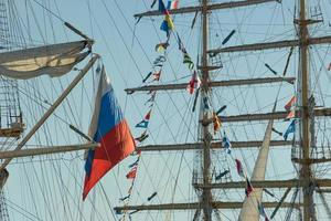 der Mast des Segelboots und die russische Flagge gegen den blauen Himmel. foto