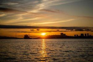 Seelandschaft mit Blick auf die Silhouette der Stadt und des Schiffes foto