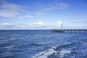 Seelandschaft mit Blick auf den langen Pier des Ferienortes mit wandelnden Menschen. foto
