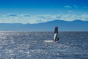 Seelandschaft mit Sportboot mit Segel und Mann. foto