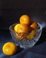 gelbe Mandarinen in einer Kristallvase auf einem dunklen Hintergrund foto