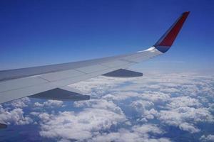 Teil des Flügels eines Flugzeugs hoch am blauen Himmel zwischen weißen Wolken. foto
