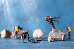 Miniaturmenschen, Taucher räumen Plastikmüllverschmutzung auf, die im Ozean weggeworfen wird, Unterwasserverschmutzungskonzept foto