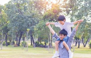 Vater und süßer Sohn spielen Papierflugzeug im Park. Der Sohn ist auf dem Rücken seines Vaters foto