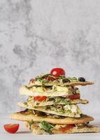 Pizza auf grauem Hintergrund gestapelt foto
