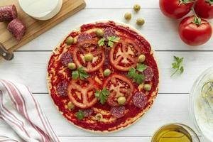 hausgemachte Pizza mit Tomaten und Oliven foto
