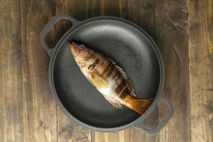Draufsicht rohen Fisch auf Teller foto
