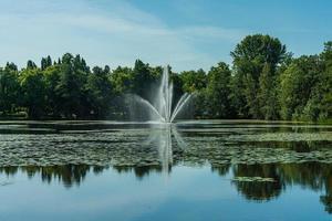 Brunnen spritzt Wasser in einen Teich foto