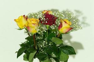 Strauß gelber und roter Rosen mit Feuchtigkeit bedeckt foto