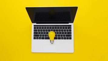 flache Lage der Glühbirne auf dem Laptop foto