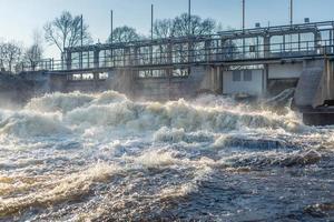 Wasserkaskaden, die aus einem Tor eines Wasserkraftwerks herausgespült werden foto