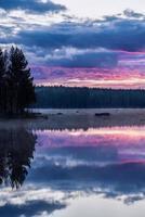 Blick am frühen Morgen überqueren Sie einen ruhigen See in Schweden foto