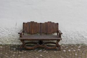 Holzbank handgefertigt auf dem Hintergrund der weißen Wände und Pflastersteine foto