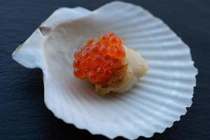 Jakobsmuschel auf einer Schale mit einer Kappe aus rotem Kaviar. foto