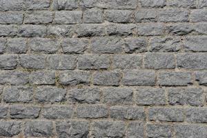 grauer Backsteinmauerhintergrund für Entwurf foto