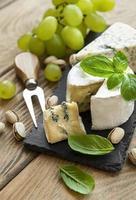 verschiedene Arten von Käse, Trauben und Nüssen auf einem alten Holztisch foto