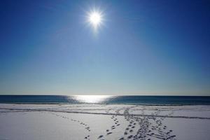 Seelandschaft mit einem Strand im Schnee und strahlender Sonne foto
