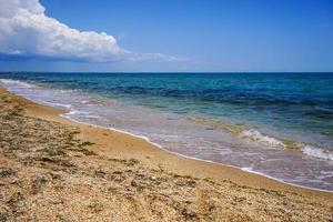 Sand- und Muschelstrand des Meeres in der Krim auf dem Hintergrund des hellen blauen Meeres und des klaren Himmels foto