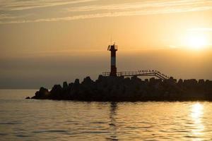 Meeressonnenuntergang mit Blick auf das Navigationslicht und die Silhouetten von Kormoranen foto