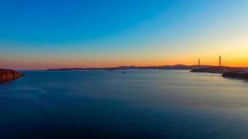 Seelandschaft mit Blick auf den Sonnenuntergang und russische Brücke am Horizont. foto