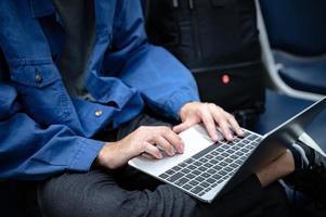 Geschäftsmann, der sitzt und einen Laptop verwendet, um am Flughafen zu arbeiten, junge Person, die reist, reist und Internet-Kommunikationstechnologie für die Arbeit hat, wenn sie drinnen an einem Flughafen auf Abflug wartet foto
