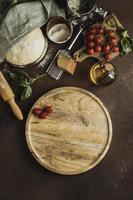 Draufsicht Pizzateig mit Holzbrett Tomaten foto