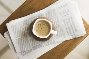 Tasse mit heißem Kaffee und einer Zeitung foto