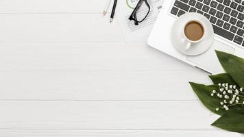 Draufsicht auf Spiralblock-Laptop mit Kaffeetasse auf Schreibtisch foto