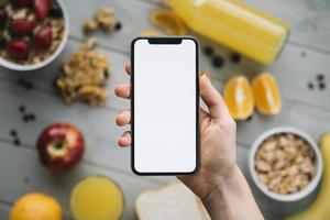 Person, die Smartphone mit leerem Bildschirmtisch mit Obst hält foto