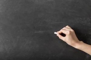 Person, die mit Kreide auf leere Tafel schreibt foto
