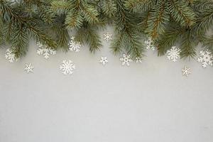 Tannennadeln auf grauem Hintergrund mit Schneeflocken foto