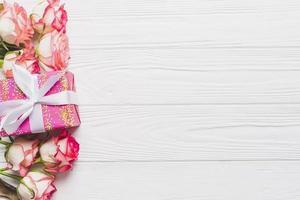 Rosen und Geschenk auf weißem Hintergrund foto