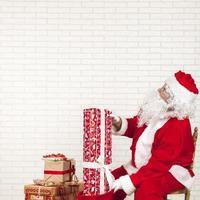 Weihnachtsmann, der Geschenke in eine Tasche steckt foto