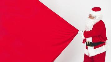 Weihnachtsmann zieht Weihnachtstasche foto