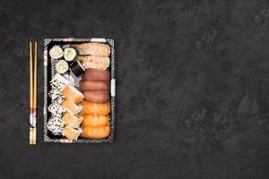 Satz gesunder asiatischer Sushi-Rollen, die in einem Tablett mit Stäbchen auf schwarzem Hintergrund angeordnet sind foto