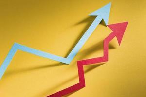 Papierpfeil, der Wirtschaftswachstum auf gelbem Hintergrund anzeigt foto