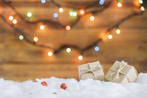 Präsentieren Sie Kisten auf dekorativem Schnee in der Nähe von Lichterketten foto