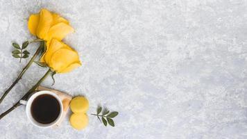 Rosenblüten mit Makronen und Kaffeetasse foto