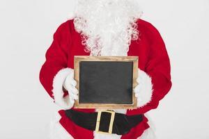 Weihnachtsmann zeigt leeren Holzrahmen foto