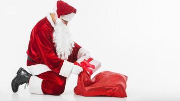 Weihnachtsmann, der Geschenkbox in Sack setzt foto