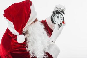 Weihnachtsmann schaut auf Uhr in Zeigern foto