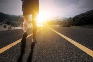 Läufer läuft in Richtung Sonnenlicht foto