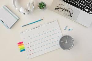 Draufsicht auf Schreibtisch mit Kalender und Laptop foto