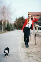 rothaariges Jockey-Mädchen in einer roten Strickjacke und schwarzen hohen Stiefeln mit einer Farmkatze foto