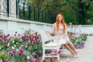 rothaariges junges Mädchen, das in einem Park zwischen Bäumen geht foto
