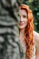 rothaariges junges Mädchen, das in einem Park zwischen Bäumen und architektonischen Objekten geht foto