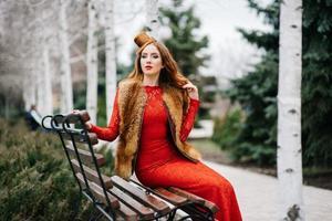 junges Mädchen mit roten Haaren in einem leuchtend roten Kleid auf einer Bank in einem leeren Park foto