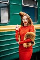 junges Mädchen mit roten Haaren in einem leuchtend roten Kleid in der Nähe eines alten Personenkraftwagens foto
