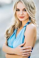blondes Mädchen in einem hellblauen Kleid in einem Granitsteinbruch foto