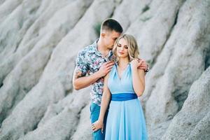 blondes Mädchen in einem hellblauen Kleid und ein Mann in einem hellen Hemd in einem Granitsteinbruch foto